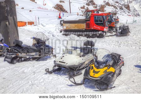 CAUCASUS RUSSIA - May 01.2015: Snow grooming and snowmobiles next to the station of ropeway on the of mountain Elbrus