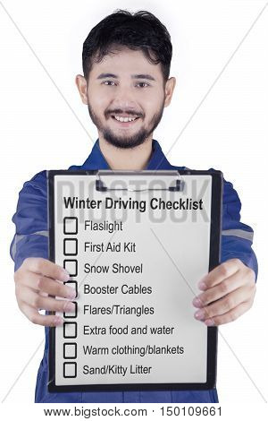 Male workshop worker smiling at the camera while showing a clipboard with winter driving tips