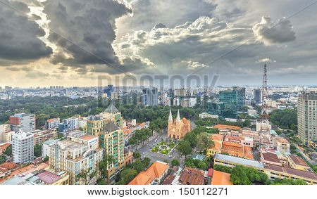 Ho Chi Minh City, Vietnam - October 2nd, 2016: Panorama Notre Dame cathedral  Beauty buildings over a hundred years old, so far is high buildings for  Economic Development in Ho Chi Minh City, Vietnam