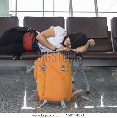 Delayed aeroplane concept. Tired passenger is sleeping on luggage in airport terminal and waiting for airplane arrival.