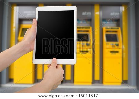human hand hold and fingerprint scan on smartphone, tablet, cell phone with blank screen on blurry cash machines background, authentication permission user concept.