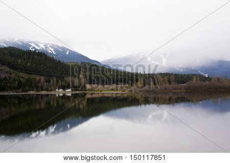 Wide view of Whistler Blackcomb BC ski hills and landscape looking across from Green lake just West of the resort on the Sea to Sky highway on a bright day in April with misty peaks and reflections.