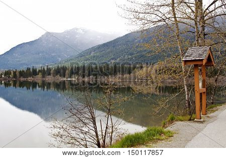 Scenic roadside stop with view of the Rockies across Green Lake near Whistler Blackcomb, BC, light mist covers the peak. Seen from the Sea to Sky highway on a bright cloudless day in April.
