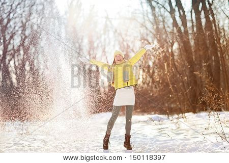 Winter landscape beautiful snowfall happy woman playing with falling snow. Asian girl having fun playfully throwing snow playing outside with arms up in the air playful on a sunny day in wintertime.