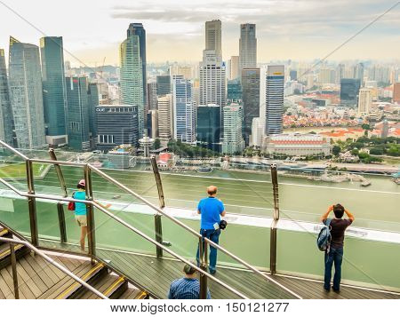 SINGAPORE, REPUBLIC OF SINGAPORE - JANUARY 09, 2014: The tourists take photo of aerial view of the Singapore city skyline. View of Singapore from Marina Bay Sands Hotel's rooftop