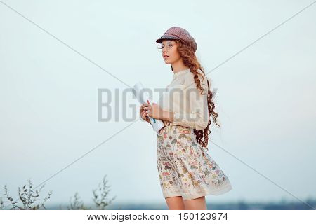 Woman writer concept. Student thinking and looking far afar standing on ashore on a slope. Joyful happy girl student sitting writing and reading outdoors on the nature.