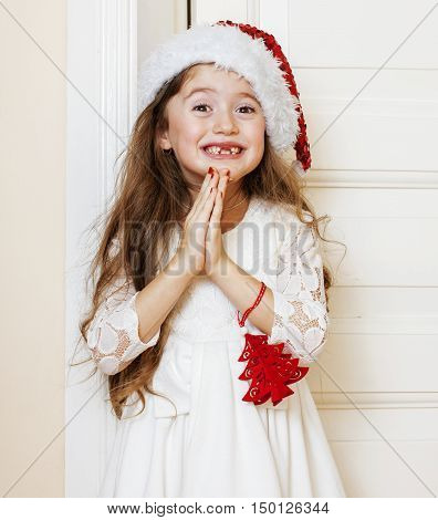 little cute girl in santas red hat waiting for Christmas gifts. smiling adorable kid. White new dress home interior close up