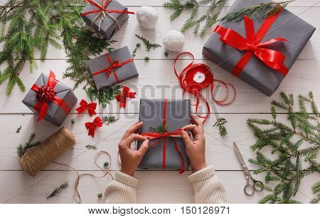 Creative hobby. Gift wrapping. Packaging modern christmas present boxes in stylish gray paper with satin red ribbon. Top view of hands on white wood table with fir tree branches, decoration of gift.