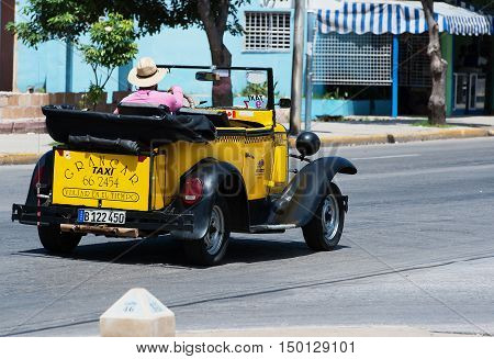Varadero, Cuba - September 11, 2016:  yellow American Cabriolet Classic Car Dirves in Varadero City, Cuba