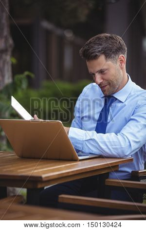 Handsome businessman using laptop and digital tablet at outdoor caf\x96\xA7