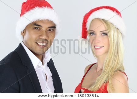 Attractive mixed couple posing for Christmas over a white background