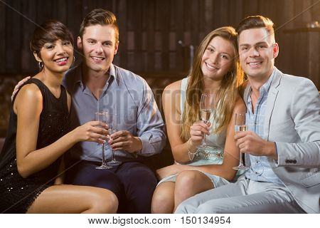 Portrait of two smiling couple having glasses of champagne at bar