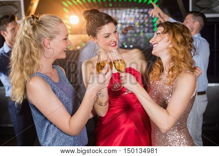 Smiling female friend toasting glasses of champagne in bar