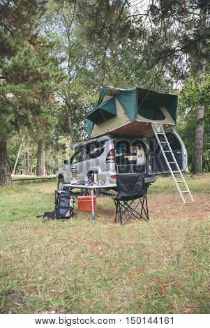 Offroad 4x4 vehicle with tent in the roof ready for camping in the forest