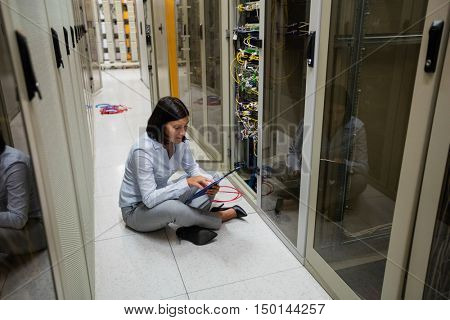 Technician sitting in hallway using digital tablet in server room
