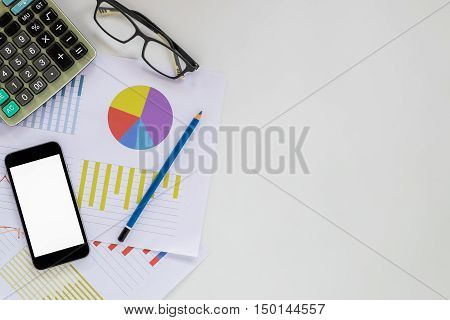 White office desk table with blank screen smartphone chart or analysis chart glasses calculator and pencil. Top view with copy space.Office desk table concept.