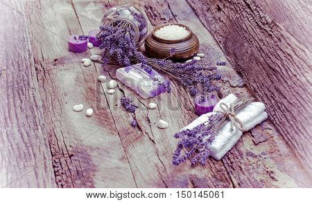 Lavender soap, scented salt and spa stones on rustic table - spa concept