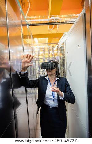 Technician using visual reality headset in hallway of server room