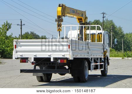 White Isuzu Flatbed Truck With Yellow Crane Arm Is In The Parking Lot - Russia, Moscow, 30 August 20