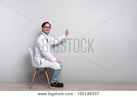 Save your health. Young handsome smiling doctor with stethoscope gesticulating while sitting on a chair on a grey background.