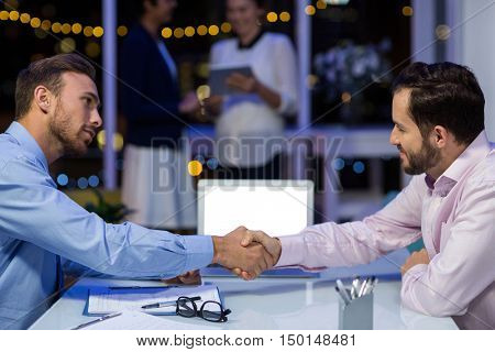 Businessmen shaking hands in conference room at office