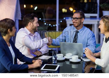 Businesspeople shaking hands while working in office at night