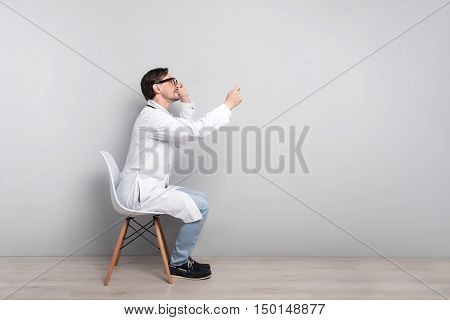 Be healthy. Concentrated young ambitious doctor sitting on a chair while diagnosing his patient with stethoscope on a grey background.
