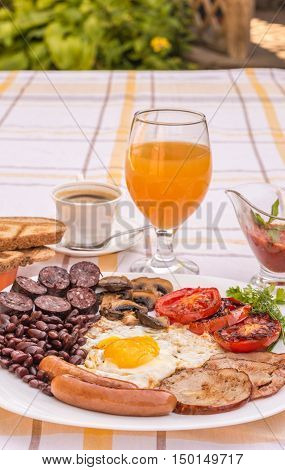 Full English fried breakfast with bacon, egg, sausages, black pudding, mushrooms. Grilled tomatoes and baked beans. Closeup with toasts, coffee, orange juice and home made  red sauce.