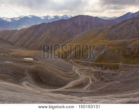 Alpine meadow in Kyrgyzstan mountains with serpentine road
