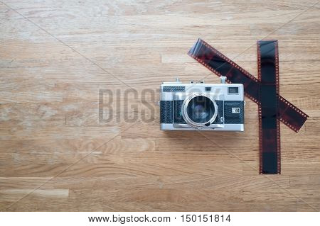 35MM film range finder camera lay on wooden table view from top with copy space