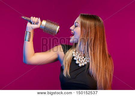 Glamourous female stylist holding a hairbrush like a microphone singing of joy
