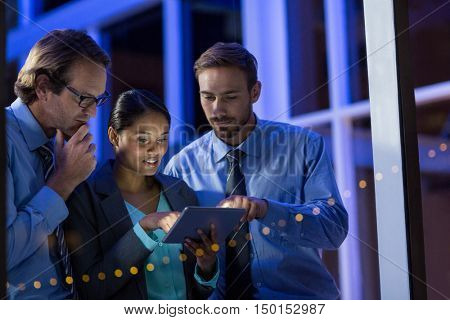 Businesspeople using digital tablet in office at night