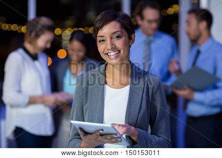 Portrait of happy businesswoman using digital tablet in office at night