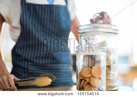 Mid-section of waitress holding jar and tong in caf\x92\xA9