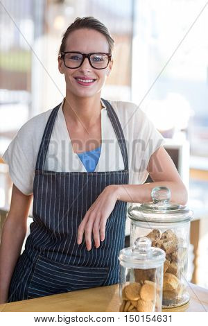 Portrait of smiling waitress standing at counter in caf\x92\xA9