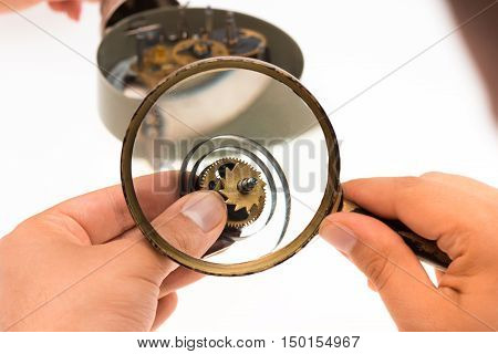 The male hand with magnifier and clockwork on white