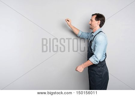 Lokk here. Positive delighted man writing on the board and smilign while being involved in work