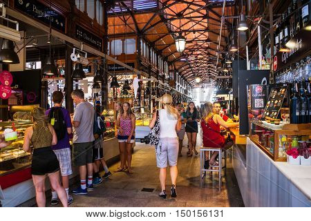 MADRID SPAIN - JULY 22 2015: People eating at Mercado San Miguel which is one of the most popular places in the city. Different food stalls drinks seafood