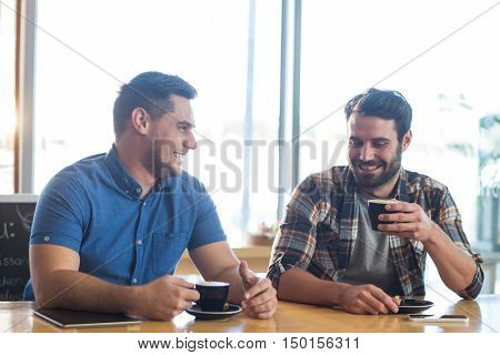 Male friends interacting while having a cup of coffee in caf\x92\xA9