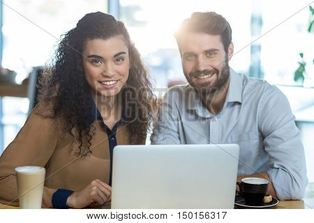 Portrait of smiling couple using laptop in caf\x92\xA9