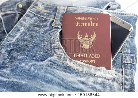 The old jeans with passport and mobile phone for prepare to traveling in anywhere.