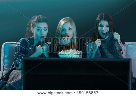 Teenage girls watching horror movie with popcorn