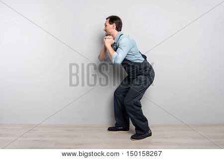 Small request. Handsome brunette middle aged man holding his hands together and holding bag while standing against the wall