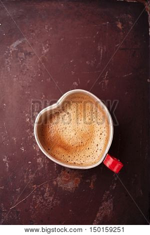 coffee in unusual vintage tin mug with red handle on old metal backdrop in heart shape