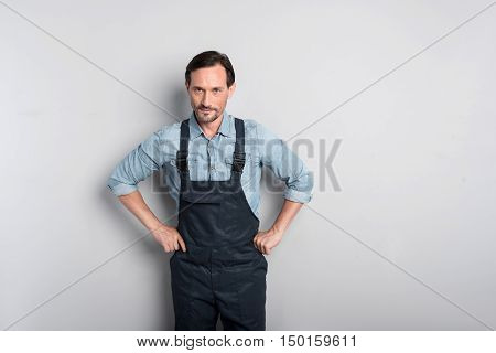 Aggressive pose. Strong handsome brunette man standing against the wall and putting his hands on his hips while looking at you