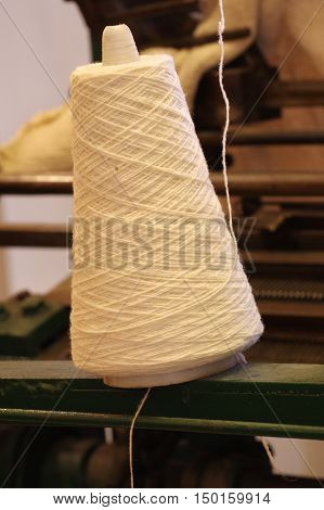Roll of woolen threads textile industry detail.