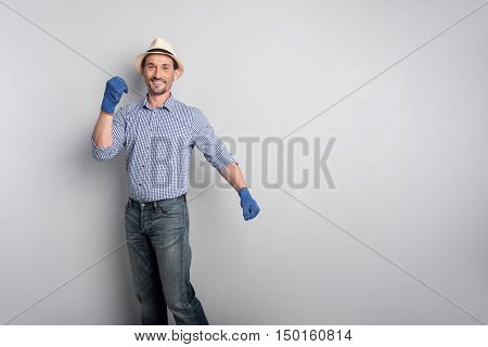 In a good mood. Delighted optimistic middle aged man moving his hands and smiling while standing against the wall
