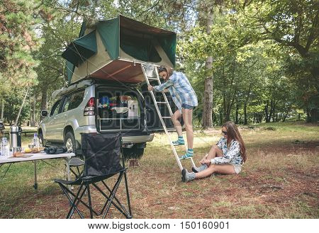 Young woman descending ladder from tent over car while other woman putting hiking boots sitting on the grass
