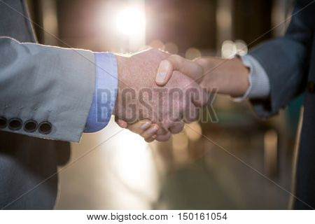 Close-up of businessman shaking hands with colleague in the office