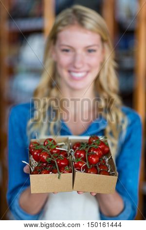 Portrait of smiling female staff holding box of cherry tomato in super market